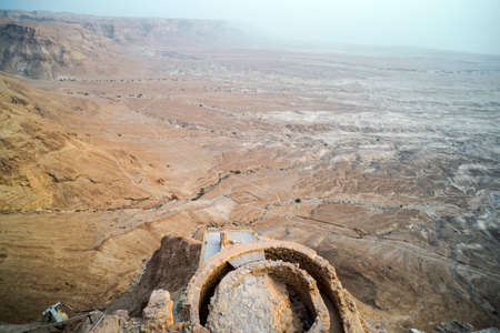 Aerial view of King Herod fortress ruins against the valley at foothills in Judean desert, Israel. Remains of ancient human buildings on the mountain platea near Dead Sea shore. Masada fort Reklamní fotografie - 124684939