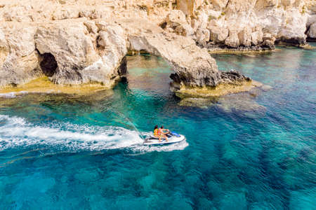 Aerial top View of The Bridge of Love or Love Bridge is located in One of the Most Beautiful Tourist Attractions in Ayia Napa, Cyprus. young couple in love riding a water bike. Stock Photo