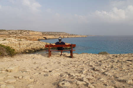 Man sitting on bench overlooking sea. A man admires the beautiful landscape. Looks away at the horizon. The guy is resting on the bench.