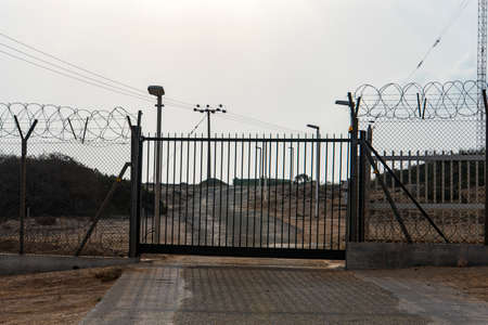 Barbed wire fence block the way. gate to a closed area. Automatic metal gate Stock Photo