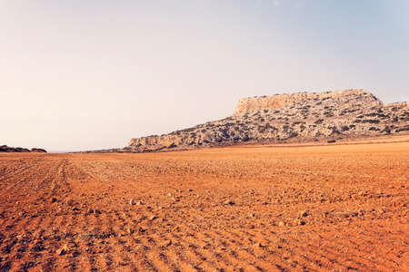 Desert on a mountain or hill background. Plowed field for agriculture. Red soil. Agricultural work. Empty field with no people.