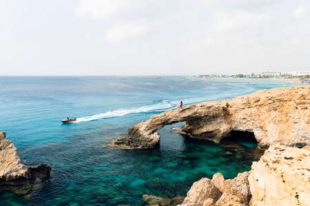 Bridge of Lovers rock formation on the rocky shore of the Mediterranean sea on the island of Cyprus Ayia NAPA. Tourists walk along the shore. Coral and stone coast, turquoise water in the sea. 免版税图像