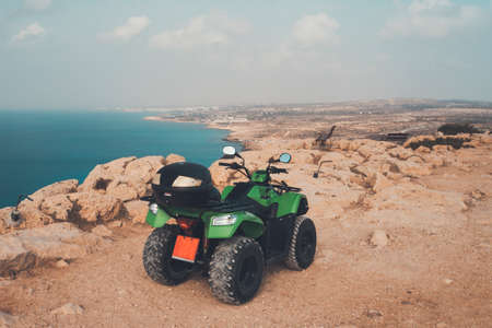 green ATV offroad on sea and sky background. Cyprus Ayia NAPA. quad bike for rent for the entertainment of tourists. Off-road driving in the desert