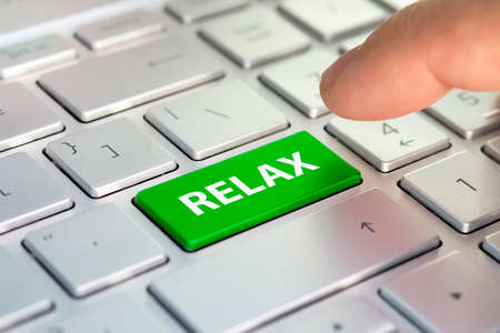 Time to relax concept. word relax written on computer keyboard. Finger presses the color button on the gray keyboard. Purchase buy tickets online. planning vacation online. Tourist agency.