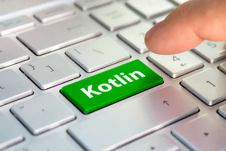 Kotlin computer language. The writing on button modern of gray laptop. Finger presses the button. Programmer for work.