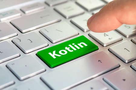 linguaggio informatico Kotlin. La scritta sul pulsante moderno del laptop grigio. Il dito preme il pulsante. Programmatore per lavoro.