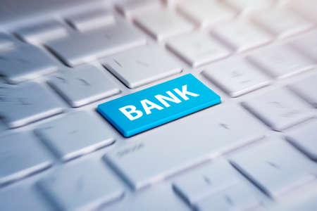 Blauwe bank toetsenbord knop. Kleurknop op het grijze zilveren toetsenbord van moderne ultrabook. opschrift op de knop. wazig in beweging achtergrond.