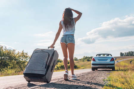 Back view of young asian woman travellerin denim shorts holding luggage and waiting car on roadside with road. concept of road travel and hitchhiking. Towards adventure.