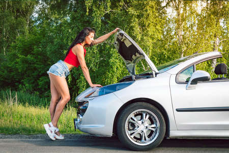 Rear view of young girl in blue short denim shorts is repairing the car. asses in shorts near a silver car with open hood. Problems with car in the road trip. brunette repairing the engine.