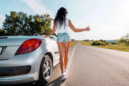 Road scene: brunette girl standing near their broken car and hitchhiking. Rear view. ran out of gas. Problems with cars on the road. Broken car. girl raises her finger. country road