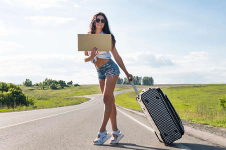 girl with tourist suitcase. hitchhiking along a road and holding cardboard, outdoor, ready for summer, vacation and travelling concept. beautiful, young brunette