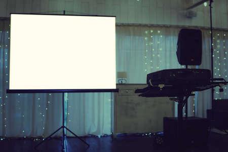 Pantalla de proyección vacía colocada en el centro de un escenario iluminado en un salón de banquetes. Equipo de pantalla de proyección en el fondo de la cortina decorada. Instalaciones para proyección de video en un evento festivo Foto de archivo