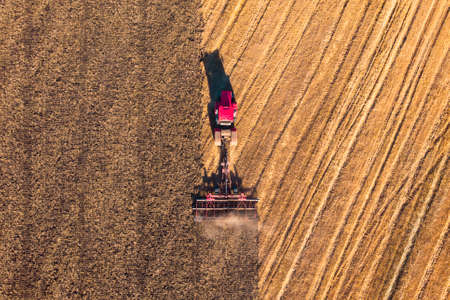 Low altitude aerial top down photo of meadow and farmer in tractor cutting grass field after this cut grass can dry and be picked up so it can be used as animal fodder for cows.