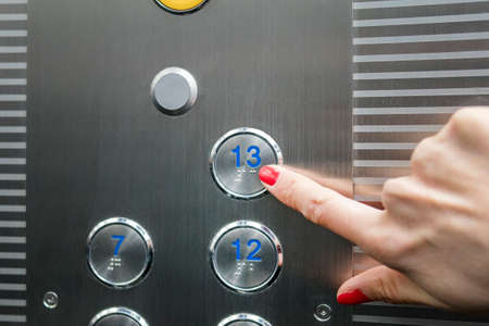 Woman in elevator or lift is pressing the button to get into the right floor only hand to be seen - close-up. 13 th floor 免版税图像 - 126576266