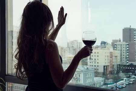 pojedynczy luksusowy piękna kobieta w czarnej sukience z winem stojący w pobliżu okna, patrząc na bok. Samotna młoda kobieta pije alkohol w domu. Alkoholizm kobiet. Zdjęcie Seryjne