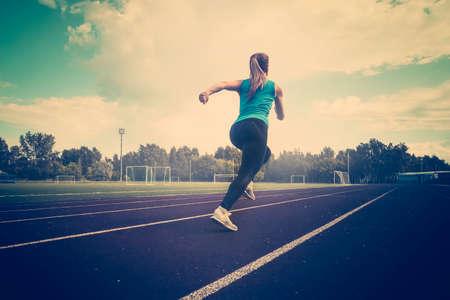 corredor de la mujer joven de la aptitud que se ejecuta en la pista. Un joven atleta corre en ropa deportiva en el estadio temprano en la mañana.