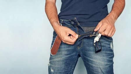Gros plan d'un homme en jeans avec fermeture éclair ouverte. pantalon bleu déboutonné