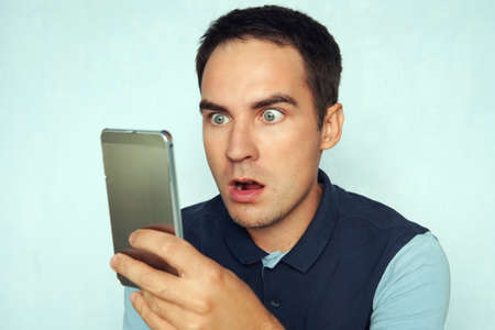 young man looks at the phone and is surprised by what he saw. Puzzled frightened expression on the face of a guy reading the news on the phone.