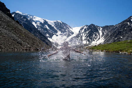 young man swimming in a mountain lake on background of beautiful mountain landscape with snow-capped peaks. Extreme entertainment. harden in cold water. cooling, overcooling, subcooling, hypothermia