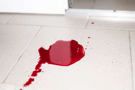 violence conceptual background which shows blood drops and splash is scary and dirty. A puddle of dried blood on the tiled bathroom floor. Stock Photo