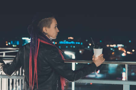 beautiful girl with coffee at night smiling against the background of garlands and city lights. coffee to go. Banque d'images - 127866200