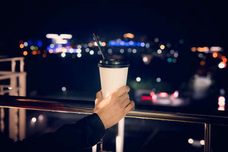 Hand holding hot coffee cup on blurred night city and colorful street night life background