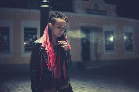 Portrait of a smoking woman. A woman with a cigarette stands at night near a street lamp. Informal model with pink hair in a black jacket and underwear. Reklamní fotografie