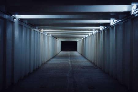 Unterirdischer Fußgängerüberweg. Ein langer Betontunnel mit Laternen in der U-Bahn der Stadt. Unterführung. Untergrundpassage