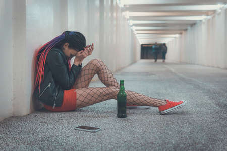 Woman crying after phone call. A young girl in depression drinks whiskey. Homeless girl sitting in despair in the underpass. Emotional experience. Foto de archivo - 127866461