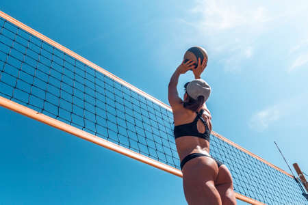 summer vacation, sport and people concept. young woman with ball playing volleyball on beach. throw the ball over the volleyball net. Banque d'images - 127867472
