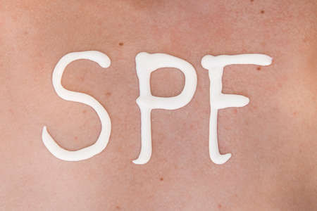 SPF word made of sunblock at woman's back at the beach. Sun protection factor concept. Close-up Banque d'images - 127867494