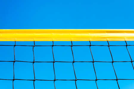 yellow colored summer games ball background - beach volleyball or tennis net against blue sky for sport events. copyspace. copy space Banque d'images - 127867497