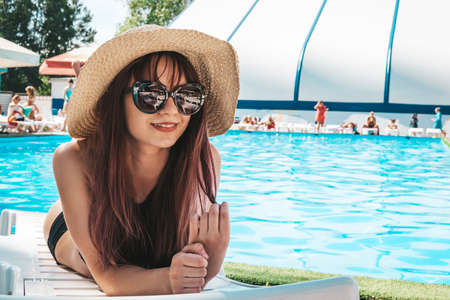 Fashion photo of sexy beautiful Girl in black top and sunglasses relaxing lying on a white chaise longue against the blue public pool. Outdoors lifestyle portrait, Fashion Beauty Swag Girl. Foto de archivo - 127867884