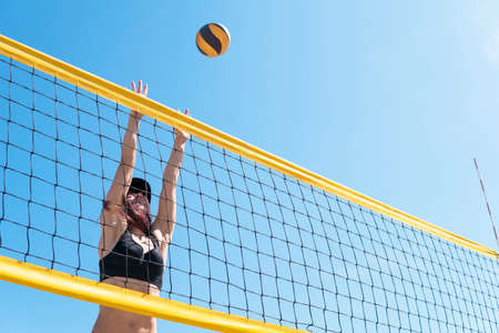 young girl playing beach volleyball. Beach volley ball match. Outdoor sports activities, vacation fun time. Banque d'images - 127867894