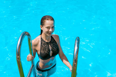 Happy young Caucasian woman wearing black swimsuit on ladder getting out of infinity pool. Summer lifestyle concept with young girl enjoying time alone at resort pool. Banque d'images - 127868068