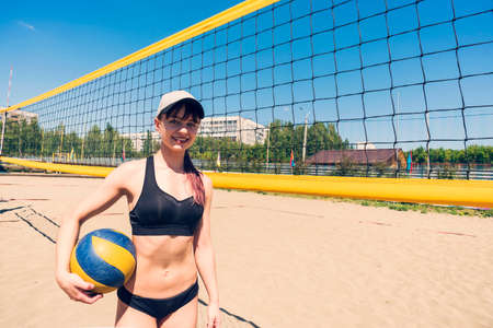 young girl playing beach volleyball. Beach volleyball championship. Outdoor sports games. A woman stands with a volleyball ball near the net on the beach.