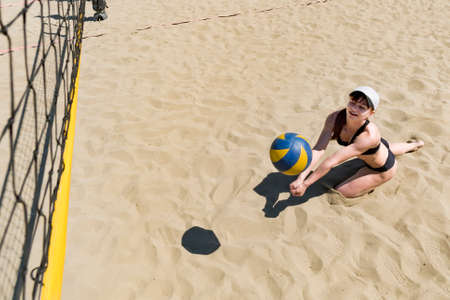 young girl playing beach volleyball. catching the ball in volleyball. taking in volleyball Foto de archivo - 127868083