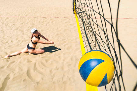 girl with a dissatisfied face falls on sand hitting the ball into net. Losing the championship in beach volleyball. Sports competition. Summer sports activities. drop to sand. volleyball ball hit net. Banque d'images - 127868077