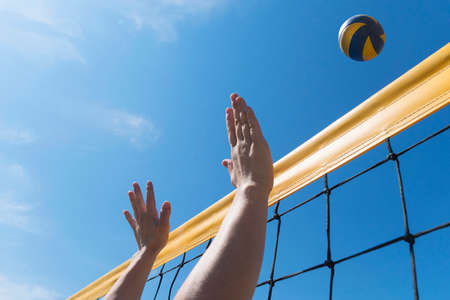 Beach volleyball woman player in action at sunny day under blue sky on beach. hands close-up reach for ball Foto de archivo - 127868105