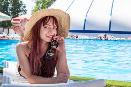 Beautiful Sexy Girl With Healthy Skin In Elegant black Bikini, Sun Hat Relaxing In Swimming Pool Water In Resort Spa Hotel On Travel Holidays Vacation. tourist lifestyle. Foto de archivo - 127868106