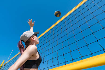 Teenage girl playing beach volleyball. Beach volleyball championship. The woman reaches for the ball. throwing a yellow volleyball over the net. Victory point. Outdoor sports games. Foto de archivo - 127868113