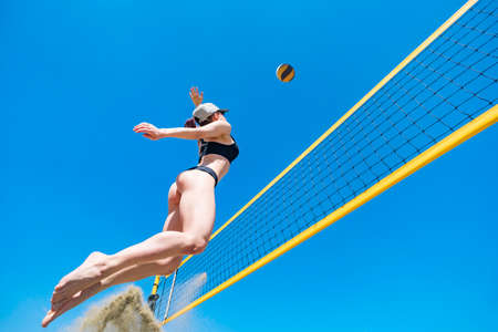 Jump of young girl, playing volleyball on beach. concept of a healthy lifestyle. Blocking the ball. match