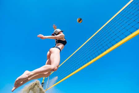Sprung des jungen Mädchens, Volleyball am Strand spielen. Konzept eines gesunden Lebensstils. Blockieren des Balls. Spiel Standard-Bild
