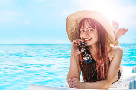 Young pretty girl lying in sun in a hat and sunbathing. remote tropical beaches and countries. travel concept. Tourist on vacation at sea. Cute smiling model in the sunlight. empty copy space for text Banque d'images - 127868117