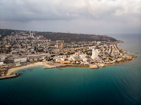 Aerial panorama of Haifa from flying drone - the third largest city of of Israel. Beautiful view of coast and seaside city on the hill. Sea shore, town, blue water and skyscape. Cityscape Banco de Imagens