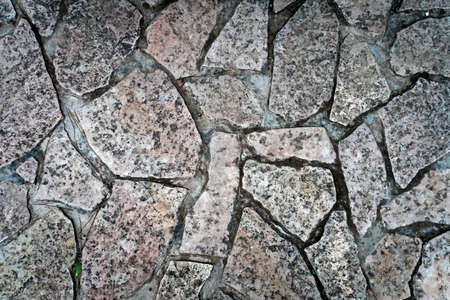 Close up of cold and wet stone path. Stone walk texture, background with cracked stone material. Abstract ancient dark granite walk. Exterior design natural materials. Ground shot from above