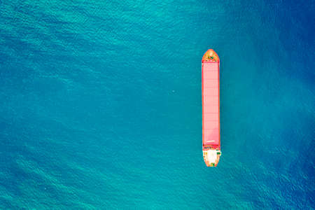 Container ship in export and import business and logistics. Shipping cargo to harbor. Water transport International. Aerial view of azure water and vertical image of red container boat. Copy space Foto de archivo - 127865641