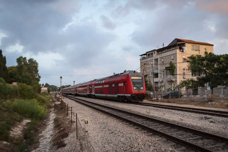 Modern high speed train on a cloudy day moving in suburbs. Railway system in Israel. Suburban train line shot in the early morning at residential building background. Concept of moving by train Banque d'images - 127868177