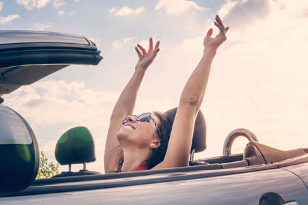 Happy girl relaxing enjoying sunshine sitting in convertible car on summer road trip vacation driving away on travel. Freedom concept woman feeling free raised his hands top. riding with wind. Reklamní fotografie