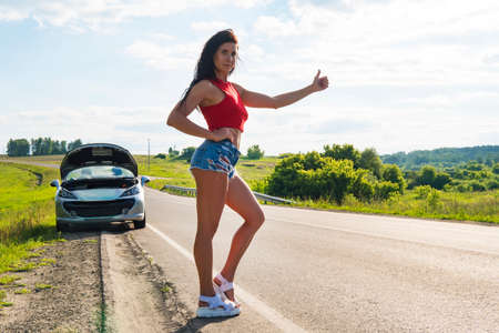 Beautiful woman hitchhiking by a broken car. girl stands at his car and waiting for help. beautiful young girl in short shorts stands at her convertible. Problem car on road. ran out of gas.